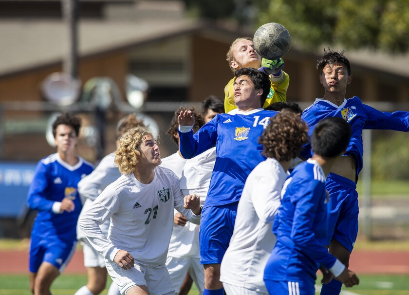 Edison goalie Bennett Flory goes up for a ball against Fountain Valley's Johnathan Swete, center, and Alan Villegas.