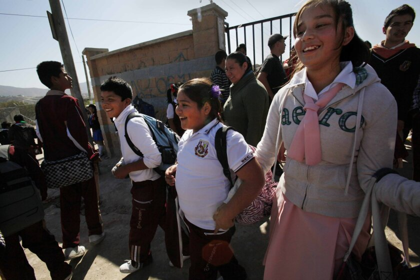 """Seventh-grader Denisse Sandoval, 12, at center, is all smiles as school lets out in Tijuana. She misses her school in San Ysidro, but is adjusting. """"I like the teachers, and how they teach me,"""" she said."""