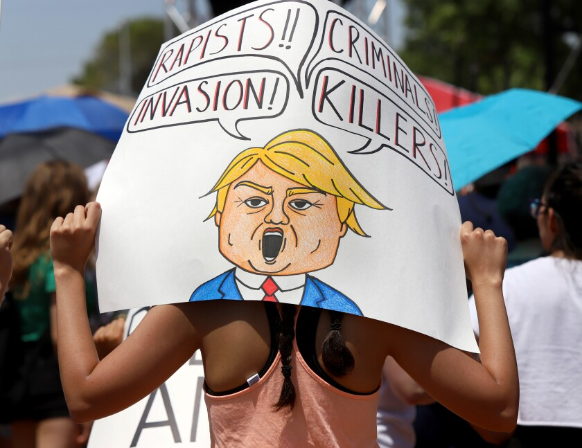 "A woman at an El Paso protest holds a sign with a cartoon Trump and speech bubbles that read ""Rapists!!"" ""Criminals!"" ""Invasion!"" ""Killers!"""