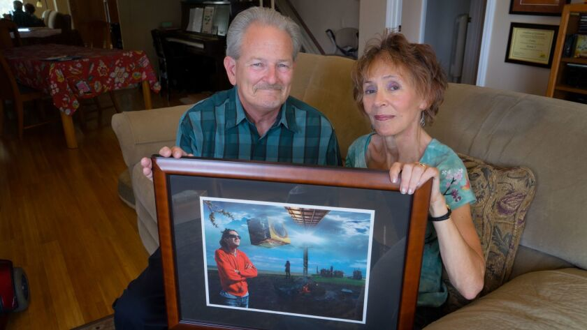 Rex and Connie Kennemer hold a photo of their 25-year-old son, Todd, at their home in Rancho Bernardo. The couple run a mental health support organization in memory of their son, who committed suicide in 2005.