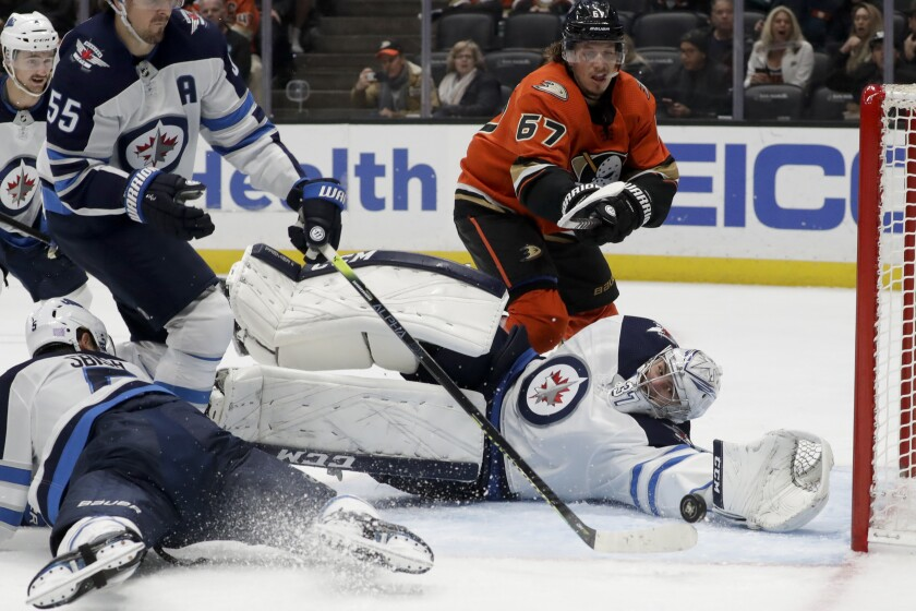 Jets goaltender Connor Hellebuyck makes a stop on a Ducks shot during the second period of a game Nov. 29 at Honda Center.