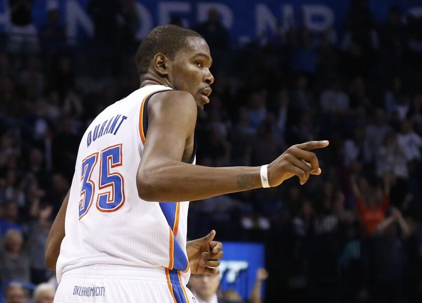 Oklahoma City Thunder forward Kevin Durant gestures to a teammate after hitting a basket in the fourth quarter of an NBA basketball game against the Memphis Grizzlies in Oklahoma City, Friday, Feb. 28, 2014. Oklahoma City won 113-107. (AP Photo/Sue Ogrocki)
