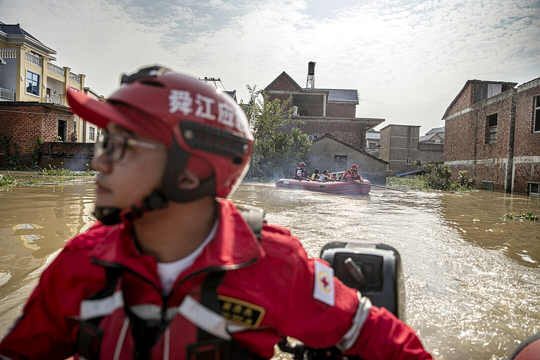 Rescue volunteers bring villagers back to retrieve items from their flooded home.