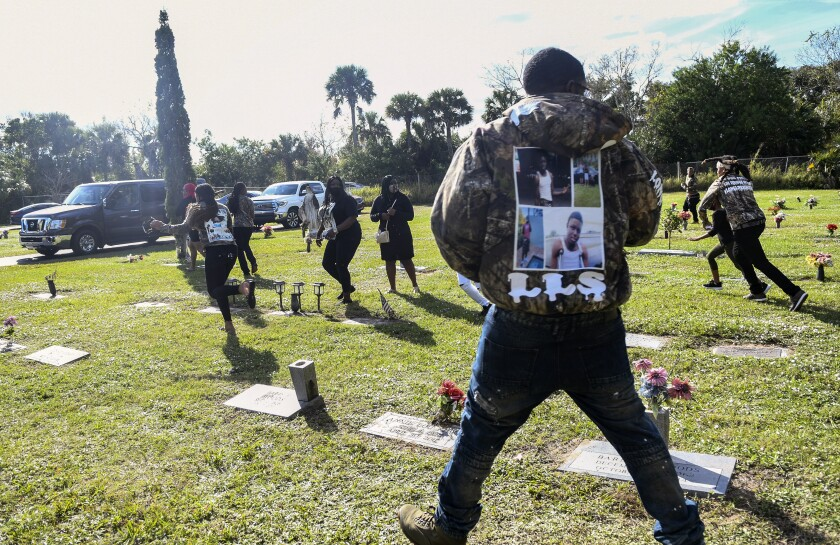 Individuals run through a cemetery after a shot was fired during a burial service