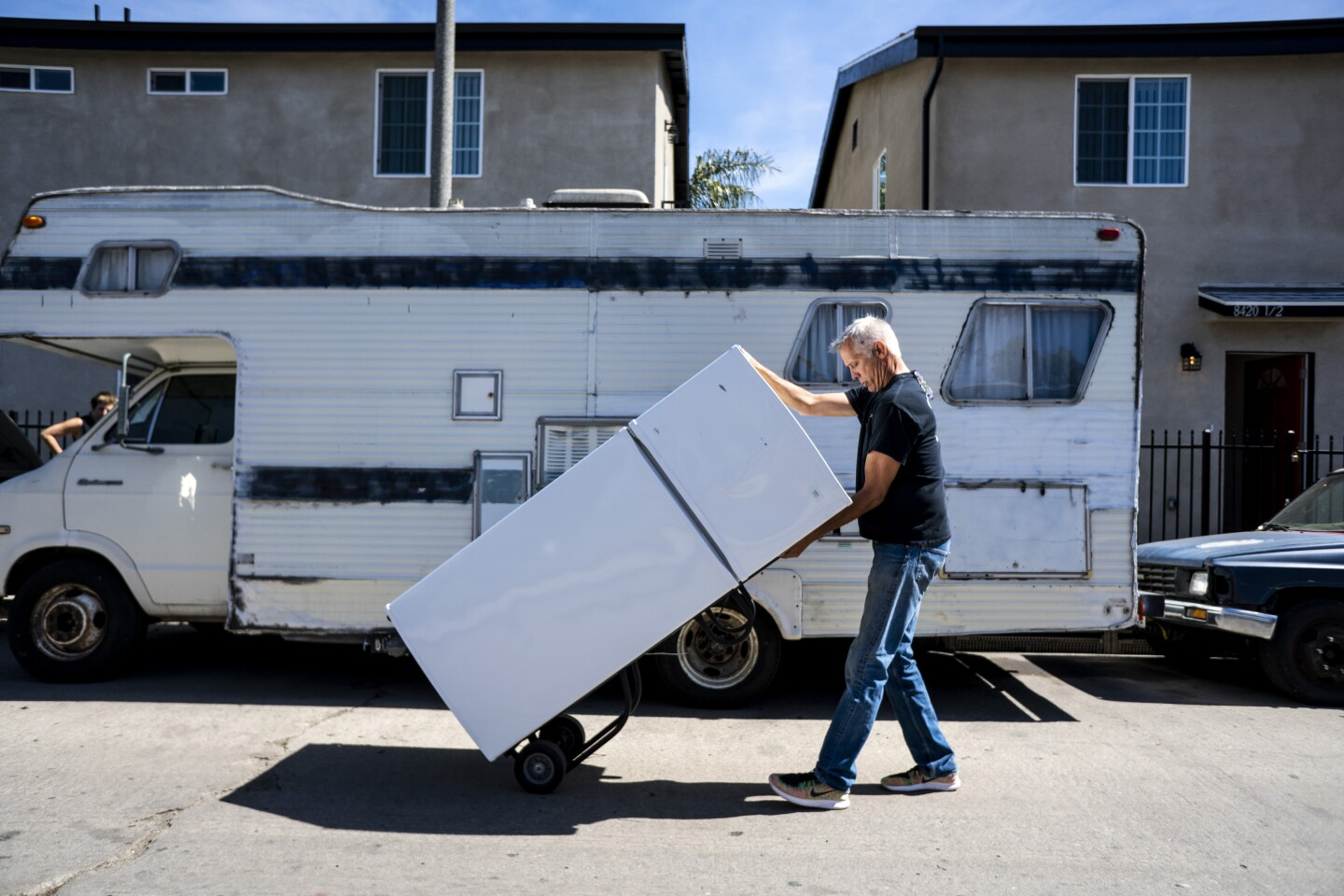LOS ANGELES, CA - MARCH 06: John Betz rolls a refrigerator down Wall street as he and Heidi Roberts (not pictured) setup two duplex housing units in south Los Angeles on March 06, 2018 in Los Angeles, California. The units, will be rented out to homeless people in what is called shared housing. (Kent Nishimura / Los Angeles Times)