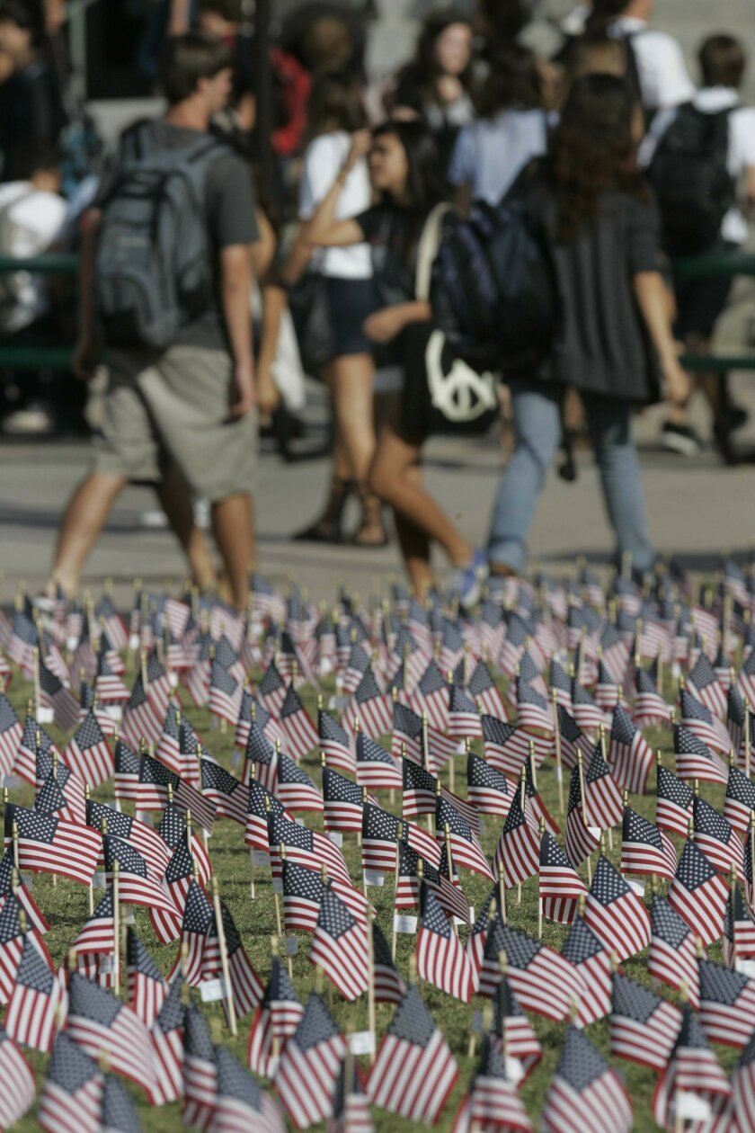 Flags bearing the names of people who lost their lives in the Sept. 11, 2001, terrorist attacks were planted in the grass yesterday at Coronado High School. (John Gibbins / Union-Tribune)