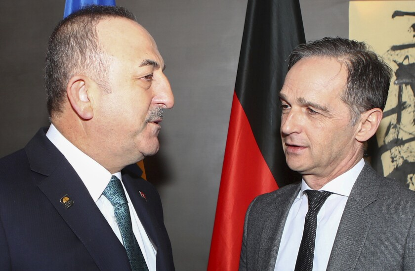 German Foreign Minister Heiko Maas, right, meets with Turkish Foreign Minister Mevlut Cavusoglu during the Munich Security Conference in Munich, Germany, Saturday, Feb. 15, 2020. (Michael Dalder/Pool via AP)