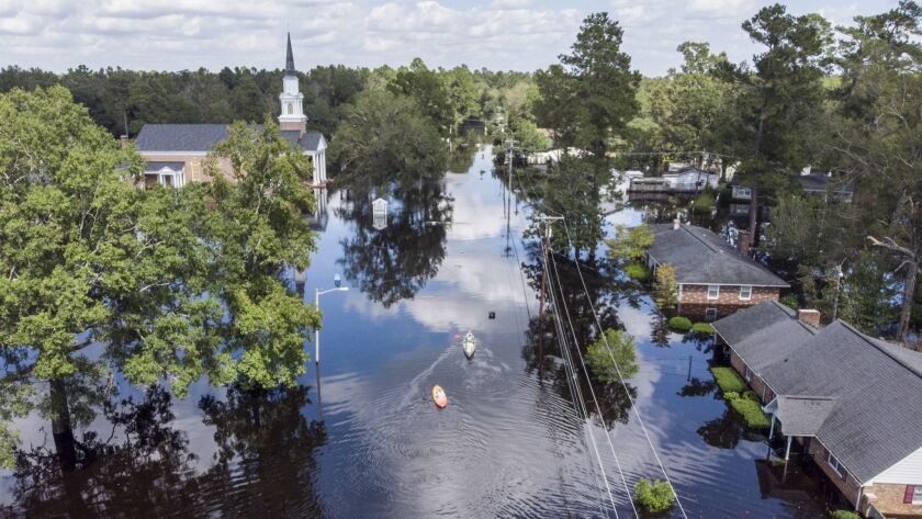 Kayaks are paddled up Long Avenue past flooded sections of the Sherwood Drive community of Conway, S.C., on Sunday.