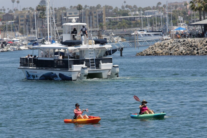 Kayakers share the Oceanside Harbor with larger boats in July 2020.