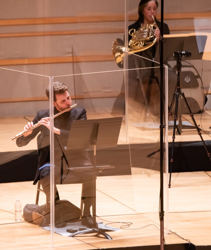 The brass and winds of the Pacific Symphony perform in a plexiglass.