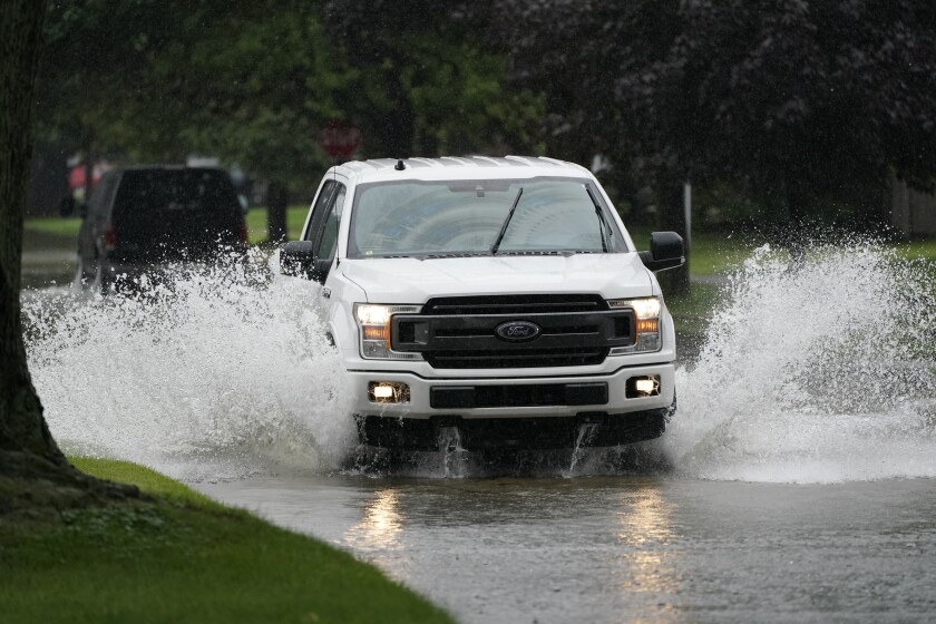 A truck drives through a flooded street, Friday, July 16, 2021, in Dearborn Heights, Mich. Detroit area residents are still drying out their basements from the flooding last month, but now more flooding is on the horizon as a heavy rain front moves through southern Michigan. (AP Photo/Carlos Osorio)