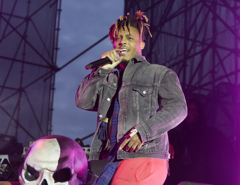 "FILE - In this May 15, 2019 file photo, Juice WRLD performs in concert during his ""Death Race for Love Tour"" at The Skyline Stage at The Mann Center for the Performing Arts in Philadelphia. The Chicago-area rapper, whose real name is Jarad A. Higgins, was pronounced dead Sunday, Dec. 8 after a ""medical emergency'' at Chicago's Midway International Airport, according to authorities. Chicago police said they're conducting a death investigation. (Photo by Owen Sweeney/Invision/AP, File)"