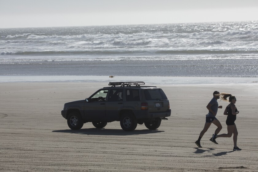 An SUV drives on a sandy beach as a couple jogs in the opposite direction.