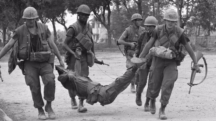 During fighting within Hue City in February 1968, U.S. Marines carry a casualty to an ambulance.