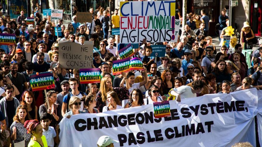 Environmental activists hold a banner reading 'Change the System not the Climate' on Sept. 8 in Paris.