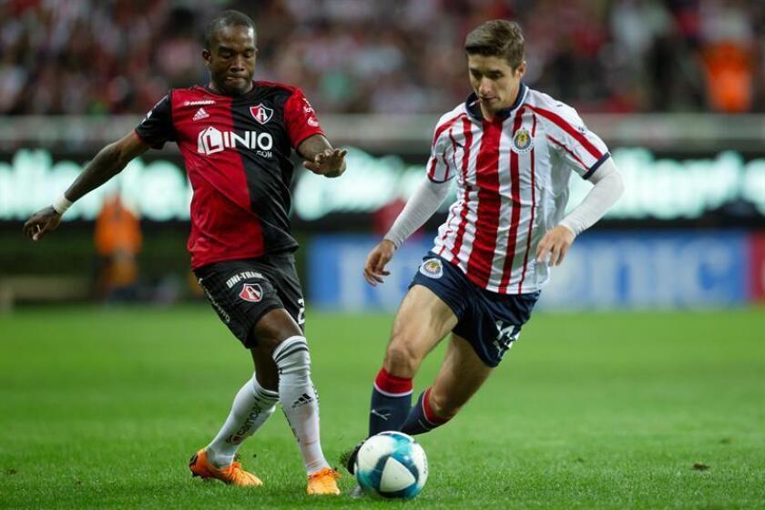 El jugador de Chivas, Isaac Brizuela (d) disputa el balón con Hernán Burbano (i) de Atlas. EFE/Archivo