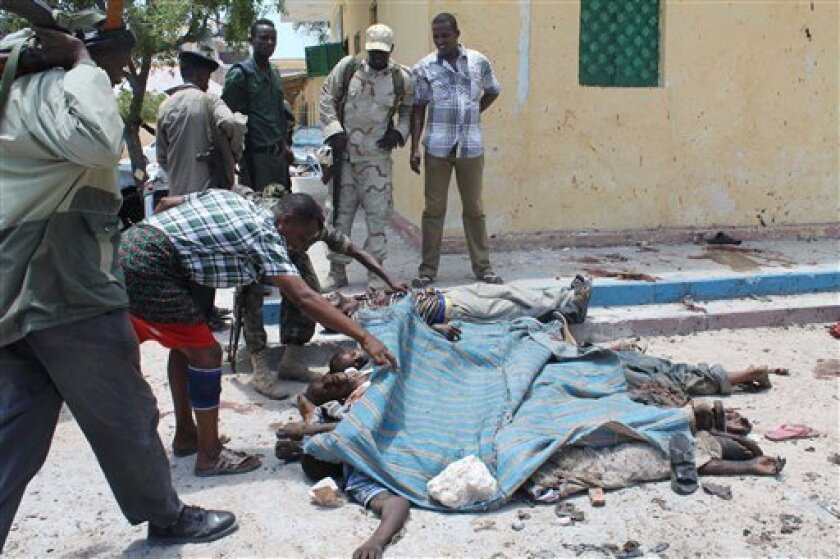 Somali soldiers look at the bodies of some of those who were killed in a suicide and car bomb blasts at a restaurant in Mogadishu, Somalia, Saturday, Sept, 7, 2013. Police in Somalia say two explosions against a restaurant frequented by government workers has killed at least 15 people. Early reports indicated that a car bomb blast and a suicide bomber attacked a restaurant near Mogadishu's State House. The restaurant, The Village, has been attacked by militants before. (Farah Abdi Warsameh)