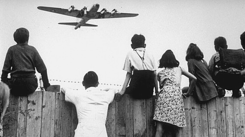 Children in 1948 West Berlin, isolated by a Soviet blockade, watch as a U.S. plane delivers food to Tempelhof Airport. Over 11 months, U.S. and British aircraft brought in 80 tons of aid, touching down every 90 seconds.