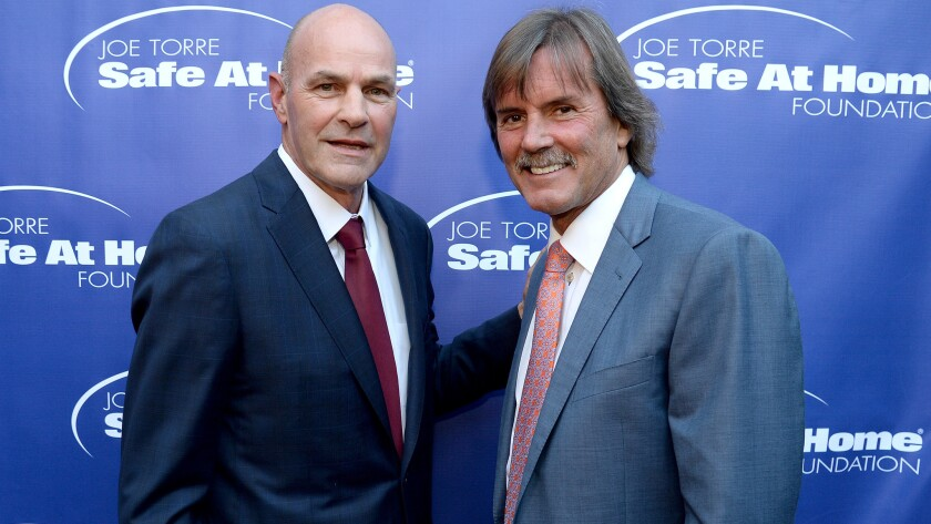 Former major league rivals Kirk Gibson, left, and Dennis Eckersley pose for a photo at Joe Torre's Safe at Home foundation event recently.