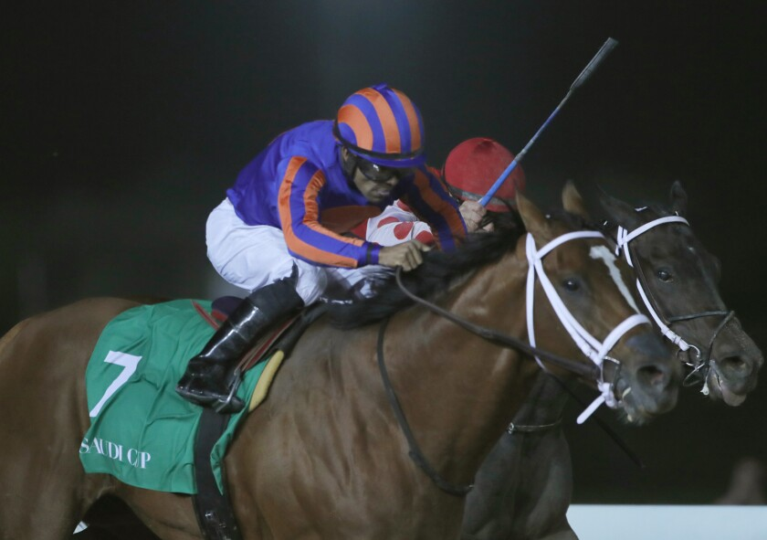 Jockey Luis Saez rides his horse, Maximum Security as he reaches the finish line of the $20 million, the Saudi Cup, at King Abdul Aziz race track in Riyadh, Saudi Arabia, Saturday, Feb. 29, 2020. The race is considered the world's richest horse race which attracted some of the world's best male and female jockeys. (AP Photo/Amr Nabil)