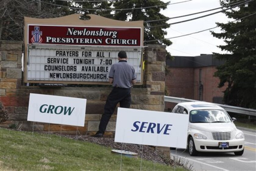Mike Kane, a parishioner at the Newlonsburg Presbyterian Church in Murrysville, Pa., works on a sign outside his church before a prayer service for victims of the high school stabbing.