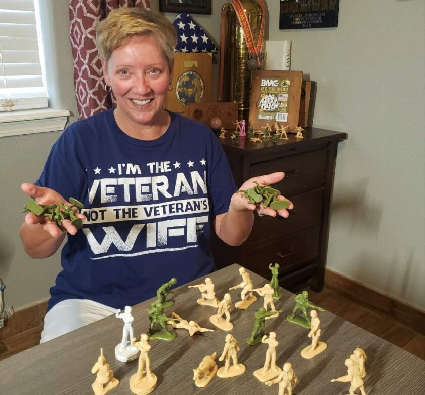 JoAnn Ortloff, proudly wearing her T-shirt, displays the first female toy soldiers by BMC Toys.