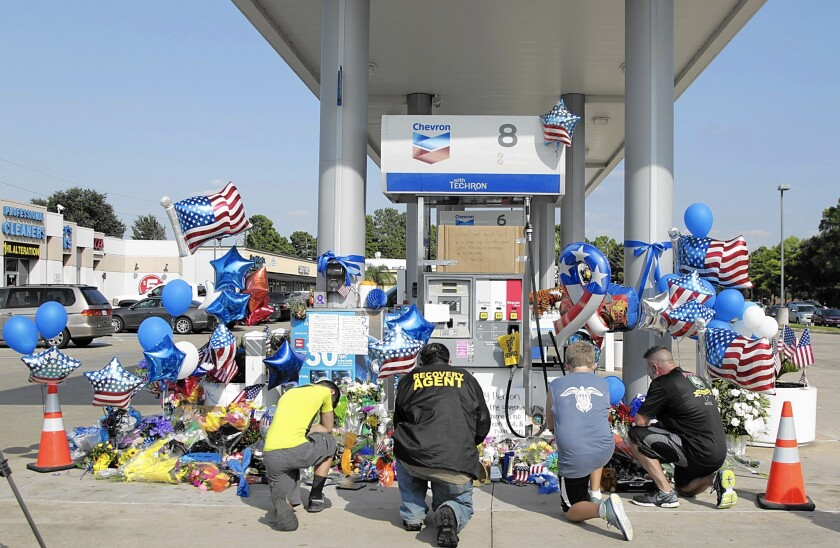 Mourners pay their respects to Deputy Darren Goforth at the Houston-area gas station where he was shot to death.