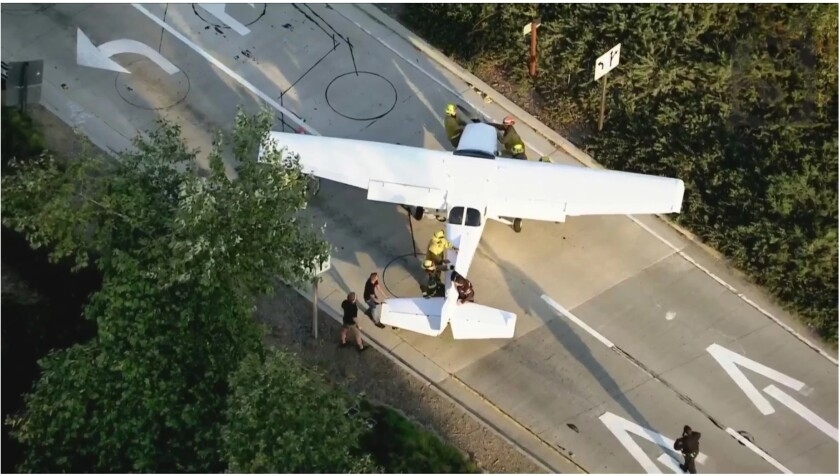 A small passenger plane is guided off a freeway