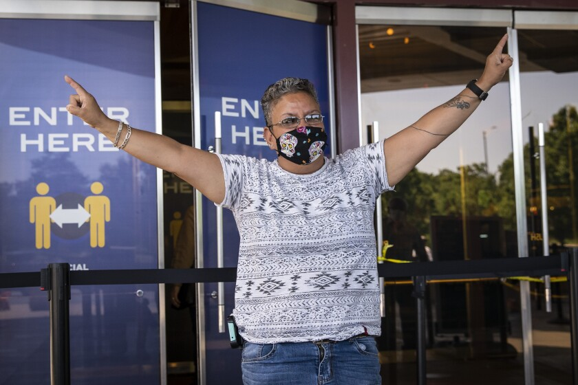 "A Mount Prospect woman who identified herself as ""Sunshine"" celebrates as she enters Rivers Casino in Des Plaines on the first day of reopening following an unprecedented three-month shutdown due to the coronavirus pandemic, Wednesday, July 1, 2020. 