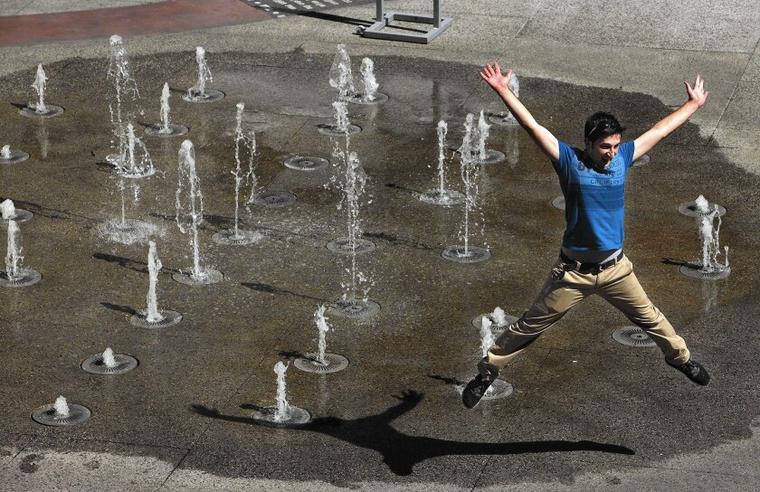 Necmettin Tekin, an exchange student from Turkey, cools off in a fountain at the Hollywood & Highland complex earlier this month.
