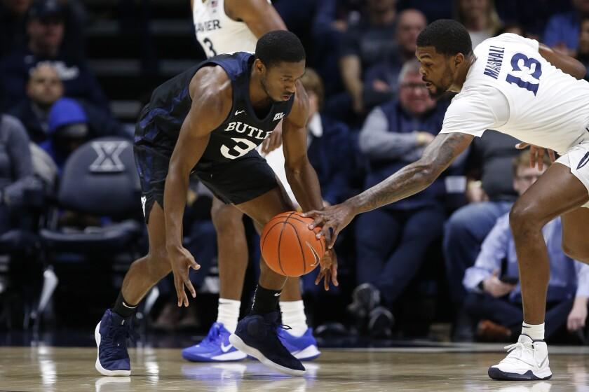 Xavier forward Naji Marshall (13) knocks the ball from the hands of Butler guard Kamar Baldwin (3) during the first half of an NCAA college basketball game, Saturday, March 7, 2020, in Cincinnati. (AP Photo/Gary Landers)