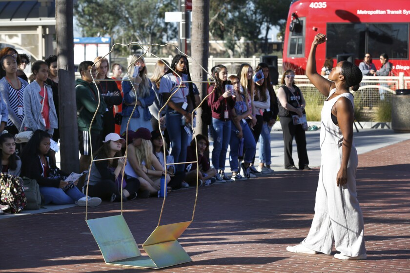 """Students and commuters watch as dancers perform """"A Configuration Reconstituting Itself"""""""