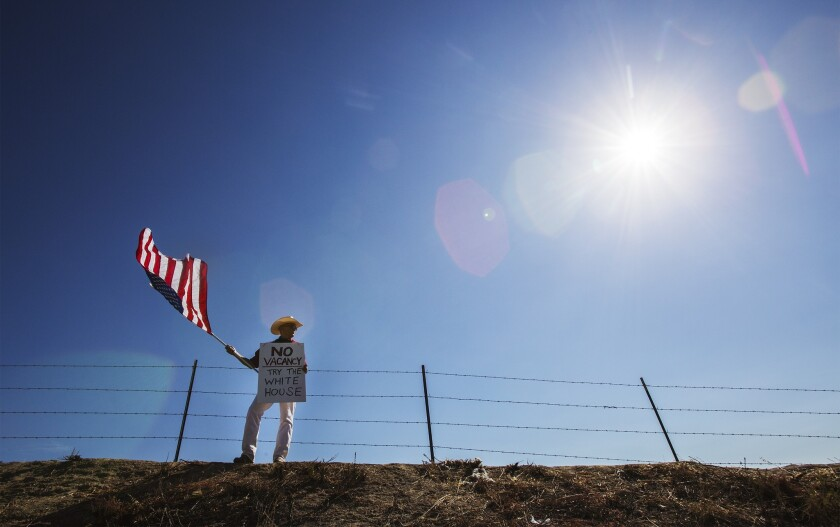 Protester William Satmary of Murrieta stands on a hill to keep a lookout for buses containing immigrant detainees.