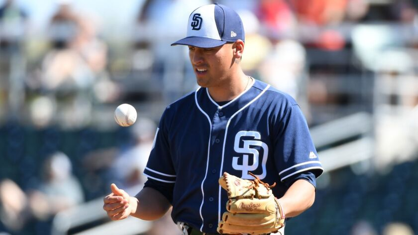 Padres reliever Gerardo Reyes flips the ball up in the air prior to stepping onto the mound in the fourth inning of Wednesday's spring training game against the Indians.