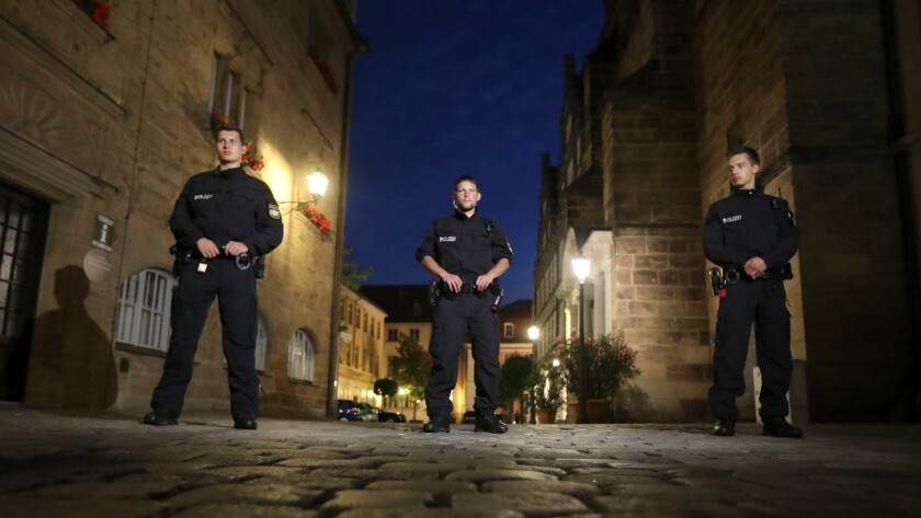 Police officers secure the area after a bomb attack in Ansbach, Germany.