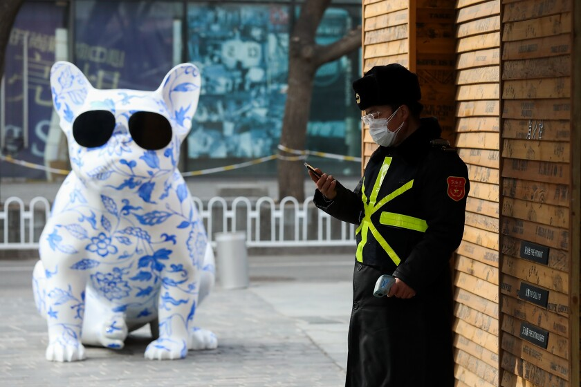 A security guard wears a protective mask outside an empty shopping mall in Beijing on Feb. 18.