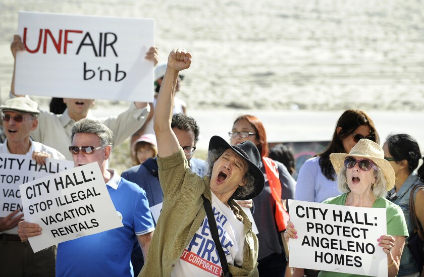 Dozens of Venice residents and affordable housing supporters hold a rally to call on the Los Angeles City Council to regulate short-term rentals and protect affordable housing in Venice.