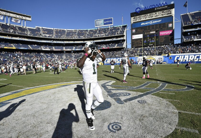 New York Jets quarterback Michael Vick (1) takes off his helmet after the San Diego Chargers beat the Jets 31-0 in an NFL football game Sunday, Oct. 5, 2014, in San Diego. (AP Photo/Denis Poroy)