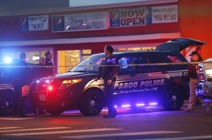 Police investigate the scene after officers shot a man to death in Pasco, Wash.