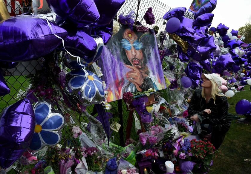 Prince fan Dawn Mitchell leaves a message beside a sea of purple balloons and flowers at a memorial wall outside the Paisley Park compound of music legend Prince, who died suddenly at 57 in Minneapolis, Minn., on April 24, 2016.