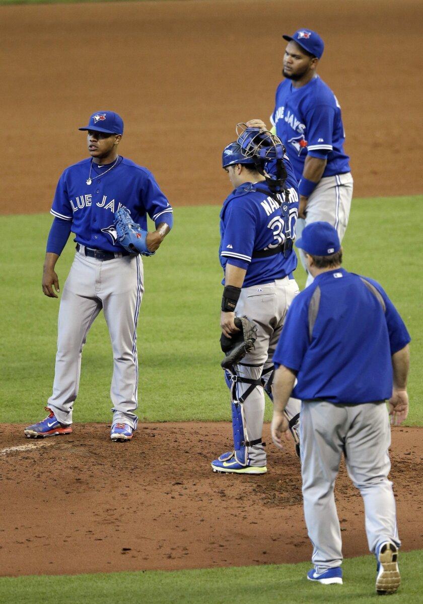 Toronto Blue Jays starting pitcher Marcus Stroman, left, looks away as manager John Gibbons, right, catcher Dioner Navarro (30) and Juan Francisco approach him after he gave up two runs in the fourth inning of a baseball game against the Houston Astros, Sunday, Aug. 3, 2014, in Houston. Stroman gave up four runs in three innings before leaving the game. (AP Photo/Pat Sullivan)