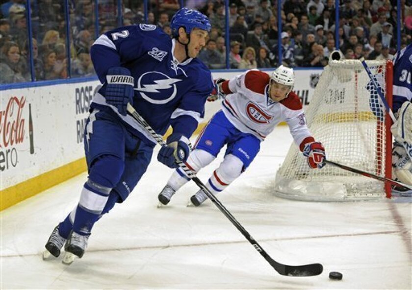 Tampa Bay Lightning defenseman Eric Brewer, left, controls the puck ahead of Montreal Canadiens center Gabriel Dumont during the first period of an NHL hockey game Saturday, March 9, 2013, in Tampa, Fla. (AP Photo/Brian Blanco)