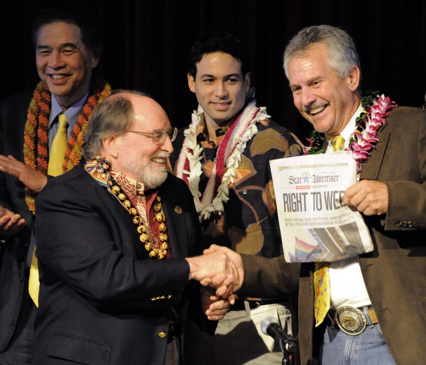 Gov. Neil Abercrombie, left, and former Sen. Avery Chumley hold a copy of the Star Advertiser after Abercrombie signed the bill legalizing gay marriage in Hawaii on Nov. 13, becoming the 15th state to legalize same-sex marriage.