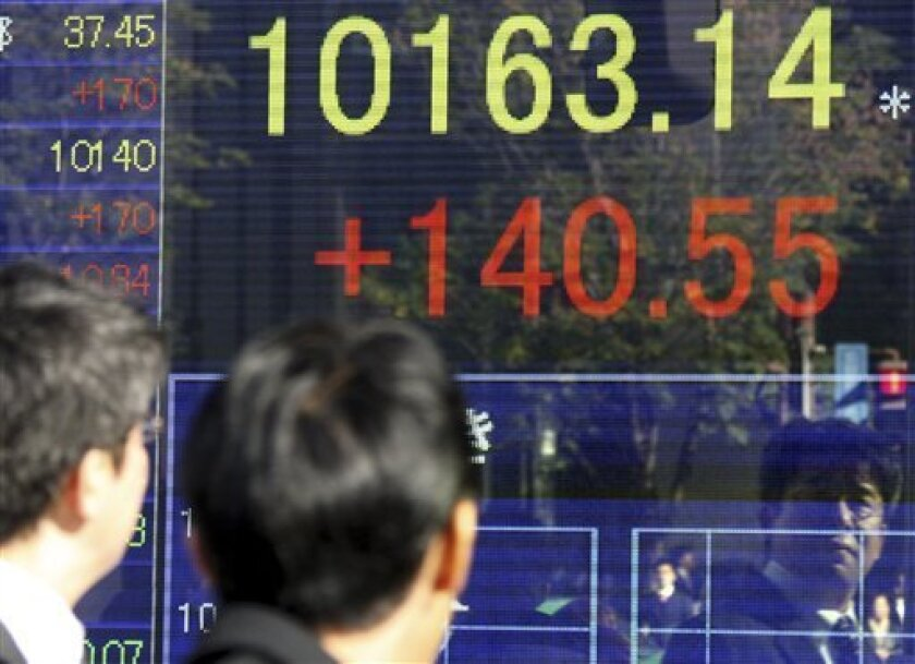 Japanese men look at an electronic stock board of a securities firm in Tokyo, Japan, on Monday, Dec. 7, 2009. Japan's benchmark Nikkei stock average rose 140.55 points, or 1.40 percent, from Friday to 10,163.14 at the end of the morning session. (AP Photo/Koji Sasahara)