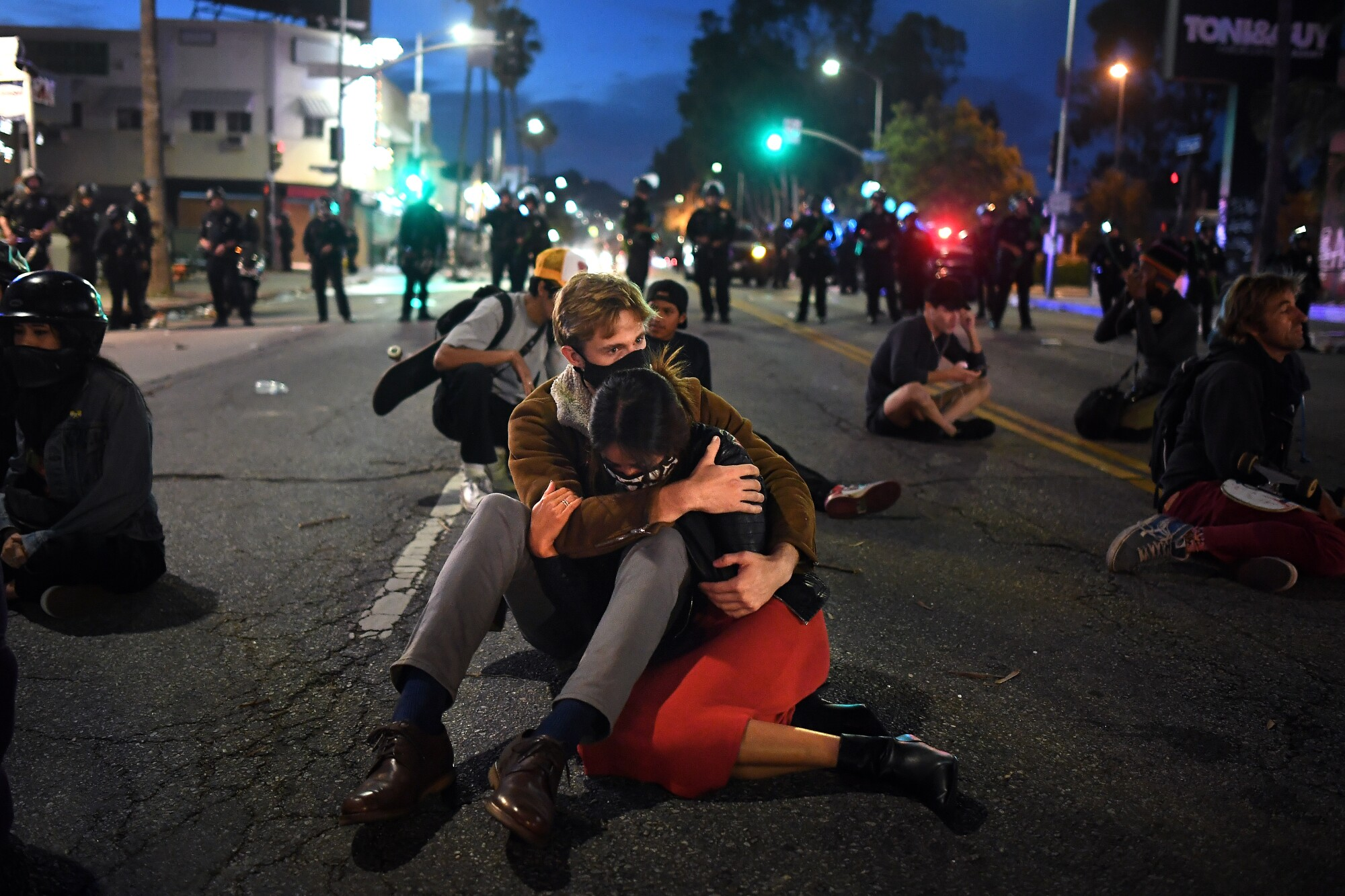 A couple who took part  in the L.A. protest protest hug on Fairfax Avenue.