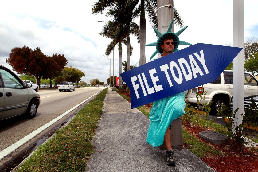 Craig Baldwin, dressed as the Statue of Liberty, holds a sign advertising a tax preparation office in Miami in 2010.