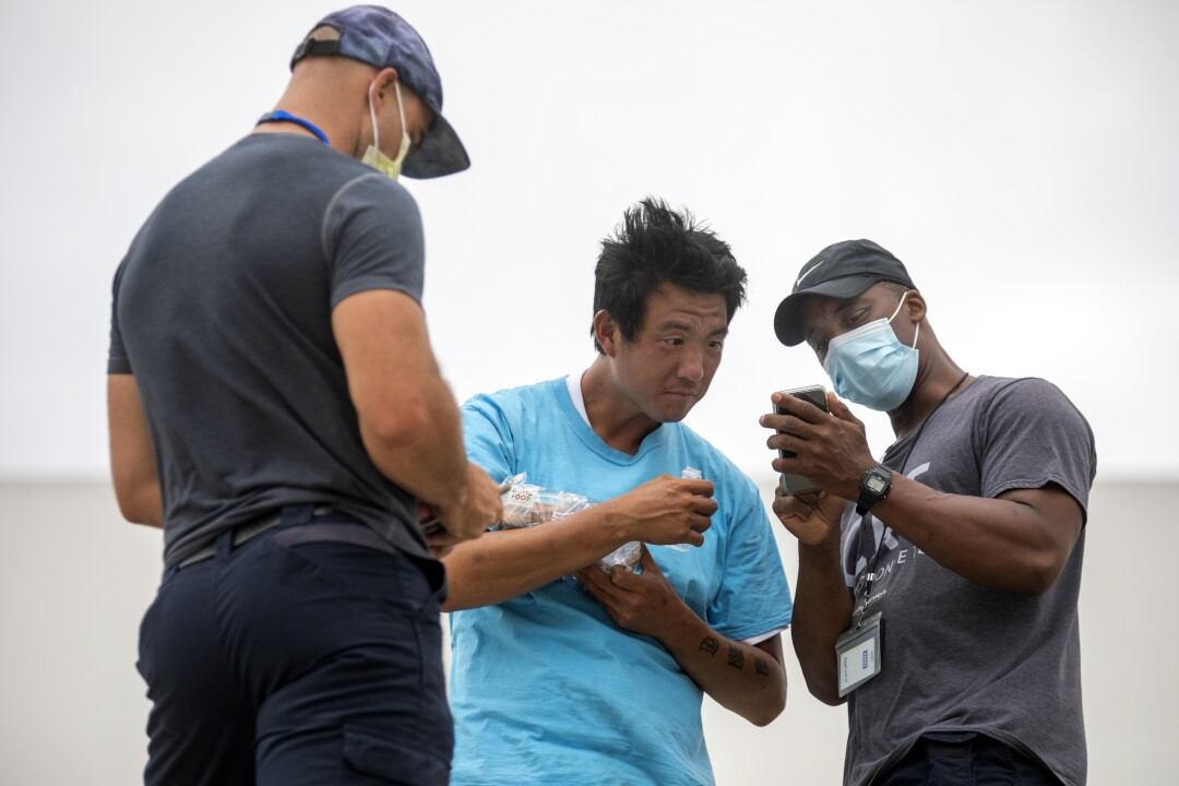 Members of the L.A. County Department of Health Services street medicine team examine a homeless man.