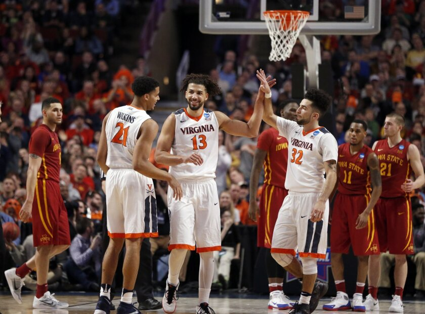 Virginia's Anthony Gill (13) celebrates with Virginia's Isaiah Wilkins (21) and London Perrantes (32) after a play in the final seconds of a college basketball game against Iowa State in the regional semifinals of the NCAA Tournament, Friday, March 25, 2016, in Chicago. (AP Photo/Charles Rex Arbogast)