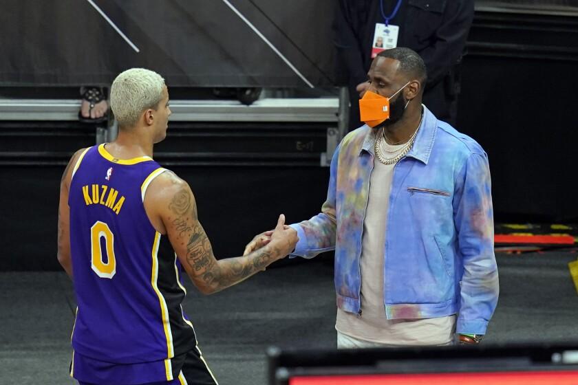 Sidelined Lakers forward LeBron James, right, greets teammate forward Kyle Kuzma.