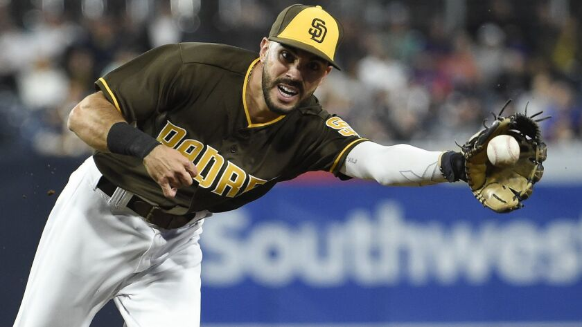 The Padres' Carlos Asuaje makes the stop on a ball hit by the Mets' Juan Lagares #12 of the New York Mets during the seventh inning of a baseball game at Petco Park on April 27, 2018 in San Diego, California.